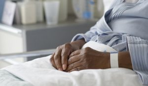 Jersey City, New Jersey, USA --- Black woman recovering in hospital bed --- Image by © JGI/Tom Grill/Blend Images/Corbis